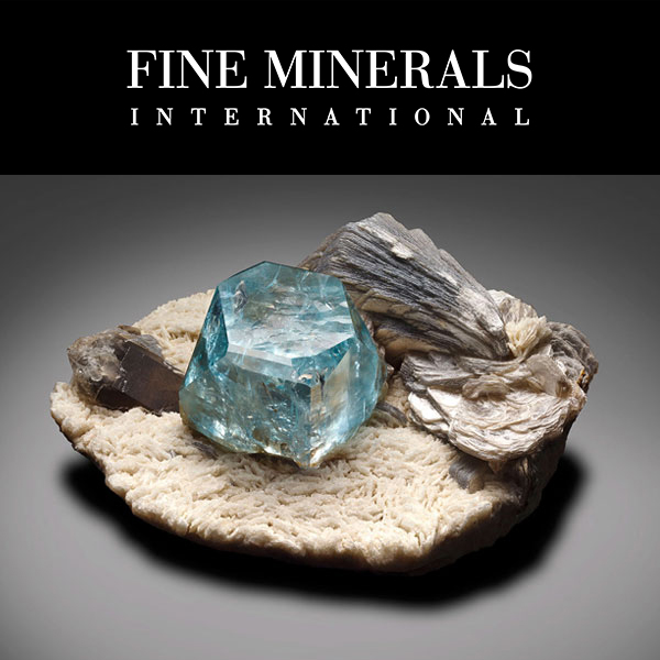 Fine Minerals International - Blue 'Pinacoid' Topaz with Muscovite and Smoky Quartz on Albite